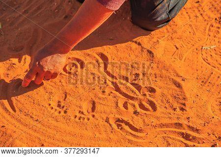 Kings Creek Station, Northern Territory, Australia - Aug 21, 2019: Aboriginal Woman Hands Creating S