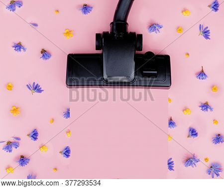 Brush Powerful Black Vacuum Cleaner On Pink Background Among Flowers. Strength, Power, Environmental