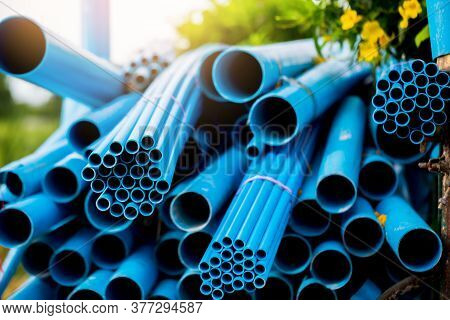 Selective To Blue Plastic Pipe Background. Pvc Pipes Stacked In Warehouse Of Construction Site.  Pvc