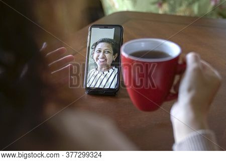 Woman With Cup Of Coffee And Having Video Call And Chat With Colleague Via Her Cellphone
