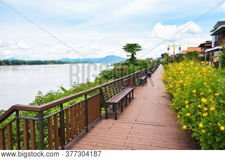 Wooden Bench Riverside Walkway Park With Yellow Flower And Blue Sky / Mekong River Chiang Khan Loei