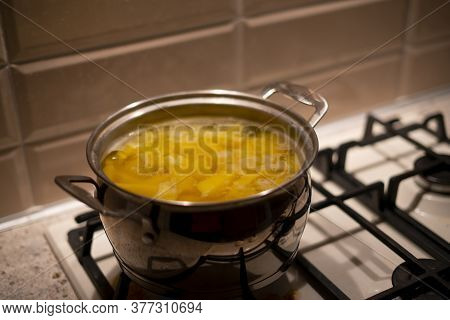 A Raw Fresh New Yellow Potato Being Cooked In The Saucepan With Boiling Water