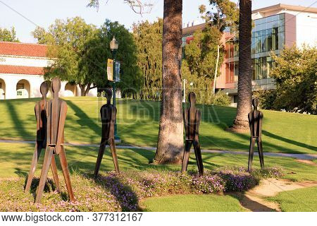 July 20, 2020 In Whittier, Ca:  Steel Art Sculptures Of People Taken On A Manicured Garden At A Cour
