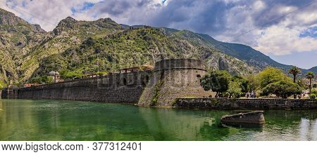 Panorama Of Kotor Bay Or Boka Kotorska, Mountains And The Ancient Stone City Wall Of Kotor Old Town