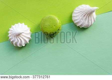 Colorful Cake Macaron Or Macaroon, White Meringues On Green, Turquoise Pastel Background. French Alm