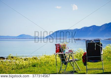 Gimsoya, Norway - July 17, 2018: Tourist Chairs And Table With Books On Grassy Sea Shore. Camping In