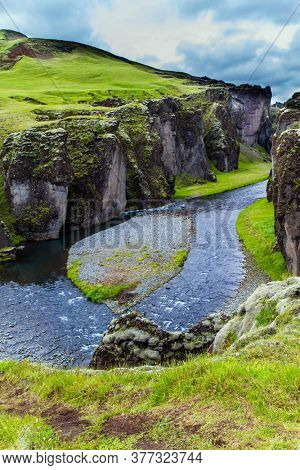 Sheer cliffs stand along a stream with melted glacial water. The most beautiful and mysterious canyon in Iceland - Fyadrarglyufur Canyon. The concept of active, eco and photo tourism