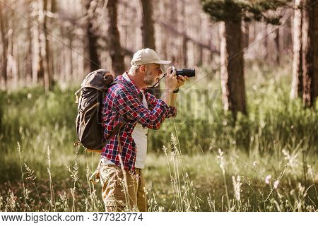 Male Hiker Photographing A Nature With Retro Camera.