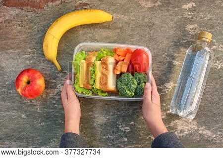 Sandwiches, Fruits And Vegetables In Food Box, Water On Old Wooden Background. Top View.