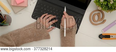 Female Student Hands Using Digital Tablet With Keyboard And Stylus Pen On White Table With Stationer