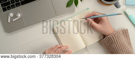 Female Student Taking Note On Blank Notebook While Doing Assignment With Laptop On Study Table
