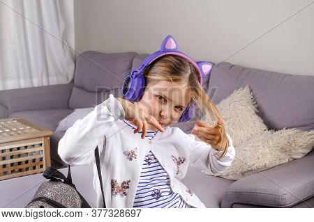 Little Girl In Musical Headphones And A Backpack Is Ready To Go To School. A European Schoolgirl Dem