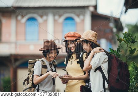 Asian Woman Group Backpacker Wearing Hat, Young Female Discussion Use Map In Mobile Phone For Travel