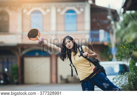Solo Female Backpacker Hitchhiking On Street. Asian Woman Traveller Hitchhiking In City.