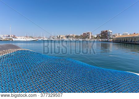 Fishing Net In The Background Of The Lagoon With Yachts. The Bend Of The Blue Nets Is Like A Sea Wav