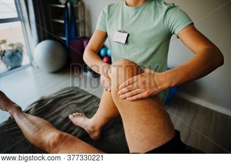 Female Therapist Treating Injured Knee Of Male Athlete Patient In Clinic, Sport Physical Therapy, Re