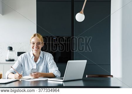 Photo of smiling young woman in eyeglasses working with cellphone and laptop while sitting at table in kitchen