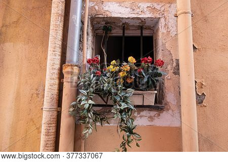 Menton, France - July 2, 2020: Flowers On A Small Neglected Window With Metal Bars And Crumbling Pla