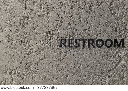 Restroom : Signage In Black Letters. Characters On The Bare Cement Wall Background. Toilet Sign, Res