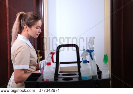 A Maid With A Cart And Attributes For Cleaning A Hotel Room.room Service At The Hotel. Concept Of Th