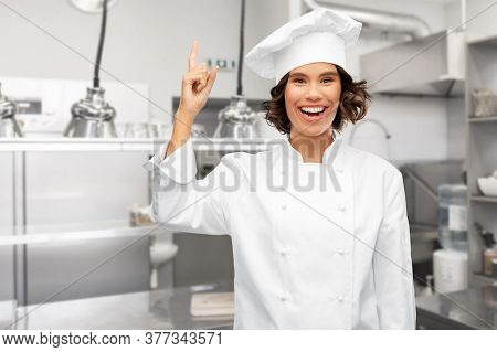 cooking, advertisement and culinary concept - happy smiling female chef in toque pointing finger up over restaurant kitchen background