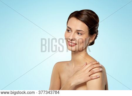 beauty, bodycare and people concept - beautiful young woman touching her bare shoulder over blue background