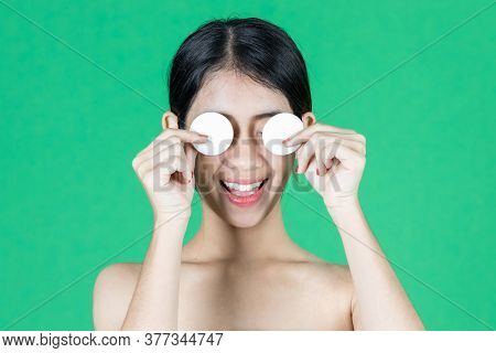 Pretty Beauty Young Asian Woman Covering Her Eyes With Cotton Pad Over Green Isolated Background. He