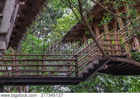 A Simple Wooden Walkway That Connect Between Two Wooden Buildings With Nature As A Background. No Fo