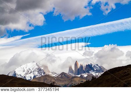 The magnificent park of Torres del Paine. Famous cliffs - Torres among clouds and glaciers. Travel to Biosphere Reserve in Patagonia. The concept of extreme tourism and photo tourism