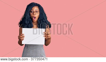 Beautiful african american woman holding blank empty banner scared and amazed with open mouth for surprise, disbelief face