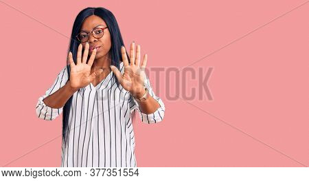 Young african american woman wearing casual clothes and glasses moving away hands palms showing refusal and denial with afraid and disgusting expression. stop and forbidden.