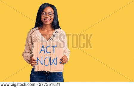 Young african american woman holding act now banner looking positive and happy standing and smiling with a confident smile showing teeth