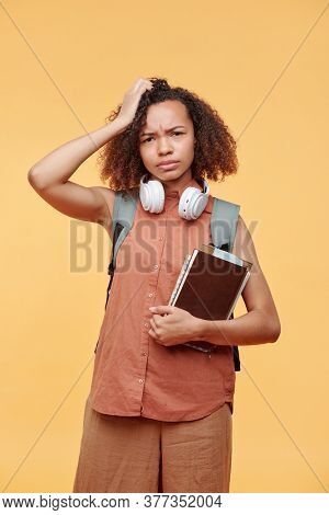 Portrait of puzzled frowning black student girl in casual outfit standing with books and scratching head in confusion