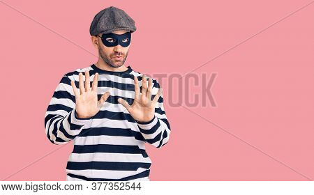 Young handsome man wearing burglar mask moving away hands palms showing refusal and denial with afraid and disgusting expression. stop and forbidden.