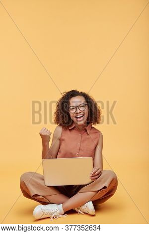 Portrait of excited African-American student girl sitting with crossed legs on floor and making yes gesture while studying online course on laptop