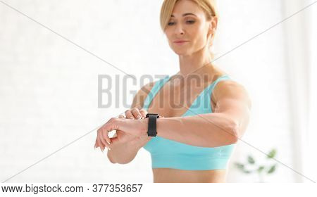 Exercises And Biological Rhythms. Attractive Fitness Adult Woman In Sportswear Checks Fitness Tracke