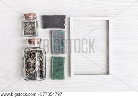 Bright Handmade Soap Bars And Natural Herbs With White Metal Frame. Flat Lay Composition With Cosmet