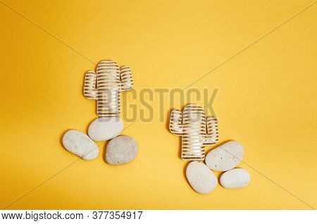 Summer Composition With Soft Toy, Two Golden Striped Cactus On Round Stones On Yellow Paper Backgrou