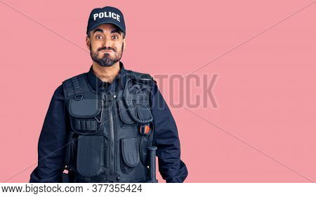 Young hispanic man wearing police uniform puffing cheeks with funny face. mouth inflated with air, crazy expression.