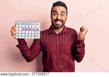 Young hispanic man holding heart calendar screaming proud, celebrating victory and success very excited with raised arm