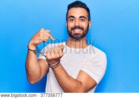 Young hispanic man wearing prisoner handcuffs pointing finger to one self smiling happy and proud