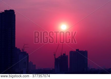 Pop Art Style Purple Pink Colored Sky With Dazzling Sun Rising Over The Silhouette Of Construction S