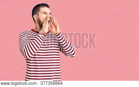 Young handsome man wearing striped sweater shouting angry out loud with hands over mouth