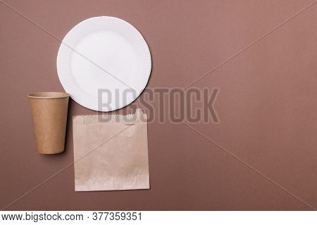 Eco-friendly Kitchen Ware, Plate, Cup, Bag, In Brown Colored Paper Background With Copy Space. Top V