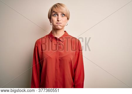 Young beautiful business blonde woman with short hair standing over isolated background puffing cheeks with funny face. Mouth inflated with air, crazy expression.