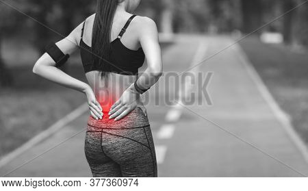 Lower Back Ache. Female Athlete Rubbing Hurt Back With Painful Injury, Touching Inflamed Zone, Black