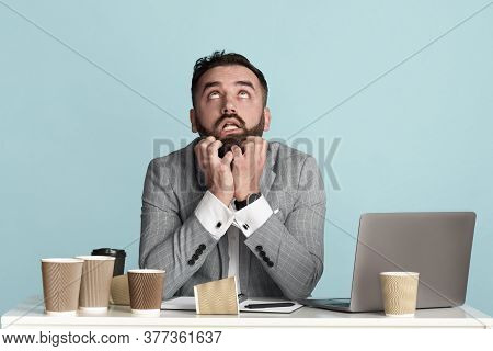 Office Employee Surrounded By Empty Coffee Cups Suffering From Work Overload At Desk On Blue Backgro