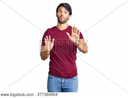 Handsome hispanic man wearing casual clothes moving away hands palms showing refusal and denial with afraid and disgusting expression. stop and forbidden.