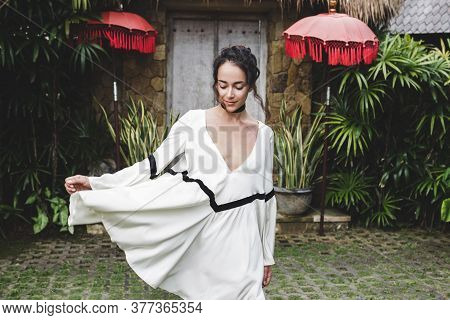Young Woman In White Tunic In Ubud Village With Traditional Balinese Architecture. Style Of Bali Hou