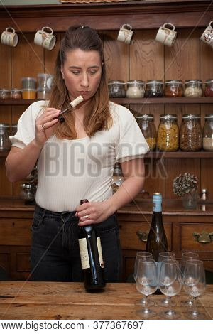 A Female Wine Taster Smell The Cork From A Bottle Of Red Wine, Taken 16th March 2020 In Abingdon, Ox